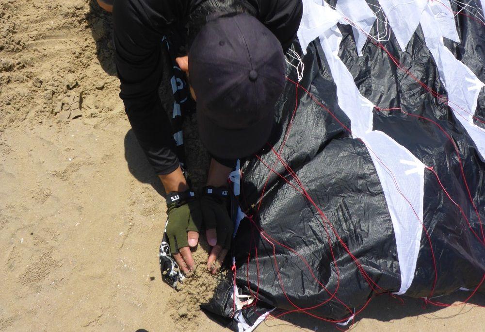 3 Verankere die Luvspitze des Drachens mit etwas Sand